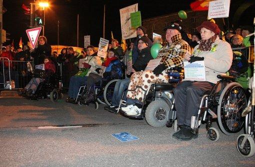 """56. Montagsdemo am 13.12.2010: Themenschwerpunkt: """"S21 – Warum Menschen mit Behinderungen oben bleiben wollen"""": Im Vordergrund einige Rollifahrer von der """"Initiative Barriere-Frei"""" und im Hintergrund viele Demonstranten."""