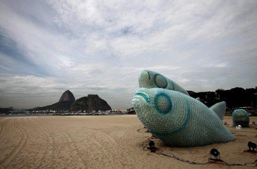 Fische, zusammen gebastelt aus alten Plastikflaschen, am Strand von Rio. Foto: EFE