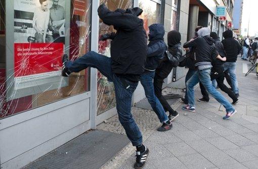 Auf Kommando traten Vermummte  Fensterscheiben einer Bank ein. Foto: AP