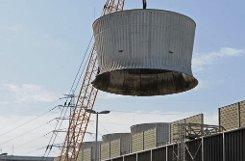 Ein Kran hebt am Donnerstag in Neckarwestheim ein Teil von einem Zellenkühlturm ab. Die beiden 186,5 Meter langen Kühlturmreihen wurden 1976 am AKW Neckarwestheim I in Betrieb genommen und stellten 2011 den Betrieb ein. Foto: dpa