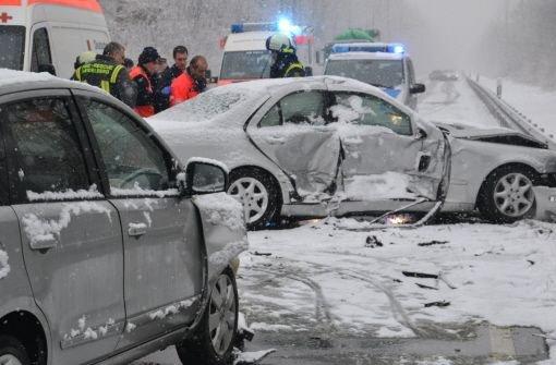 Rettungskräfte stehen am Freitag auf der schneebedeckten B 292 bei Walldorf nach einem Unfall hinter zwei beschädigten Fahrzeugen. Foto: dpa