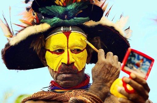 Ein Huli-Krieger aus Papua-Neuguinea schminkt sich für eine Tourismusmesse. Foto: dpa