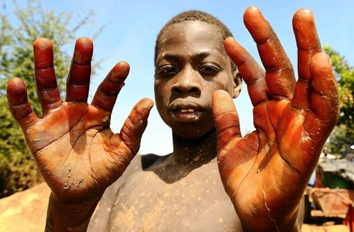 Ein Kind, das in einer Goldmine in Burkina Faso arbeitet, zeigt seine Hände. Mit Henna versucht man dort, die Haut vor Quecksilber zu schützen. Foto: dpa