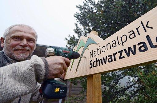 Nationalpark-Direktor Wolfgang Schlund bringt schon mal ein Hinweisschild an. In unserer Bildergalerie werfen wir einen Blick auf die Geschichte des Nationalparks. Foto: dpa